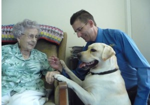 A nursing home resident with Lex the labrador and Justin Jordan